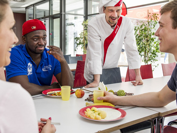 Group of people talking to a Sodexo chef