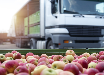 Crate of apples with a lorry in the background
