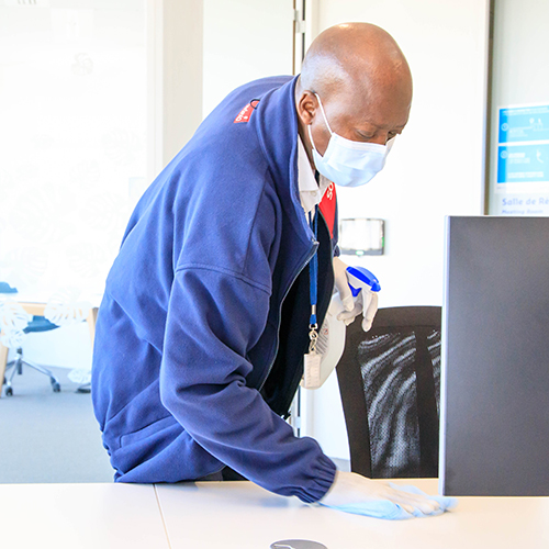 Man cleaning office wearing a mask and gloves