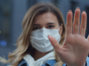 woman wearing a mask with her hand out to the camera