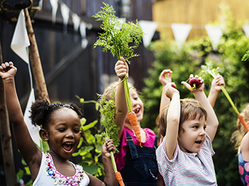 Children holding up vegetables in a vegetable garden