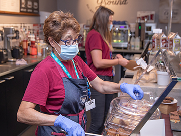 Employee serving food, wearing gloves and a mask