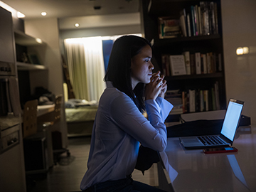 woman sitting in front of laptop in a dark room