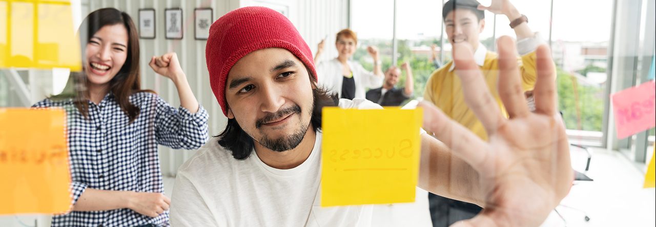 Homme pointant des post-its sur un tableau transparent