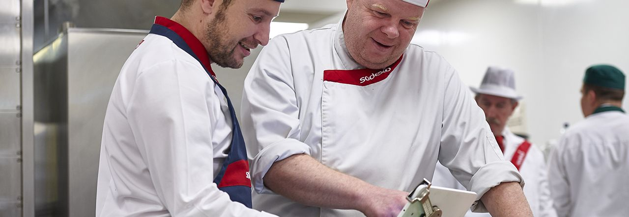 Two chefs using a tablet