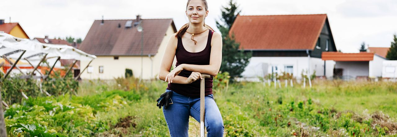 Farmer with in a foot on a fork, in a field
