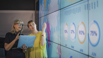Two business women discussing global statistics on a large colorful information wall, in a dark meeting room