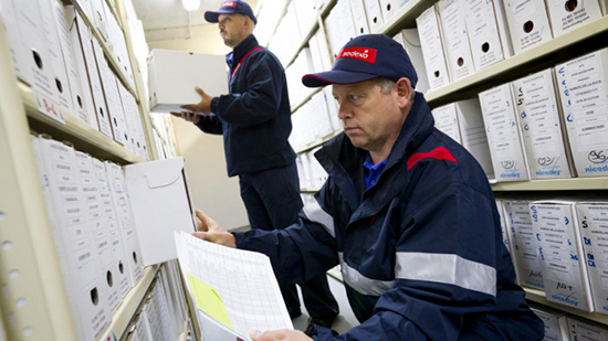 Two Sodexo employees sorting archived boxes of documents