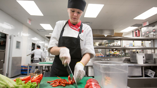 Sodexo chef cutting tomatoes in a kitchen
