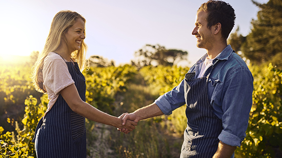 Man and woman wearing aprons over their clothes and shaking hands