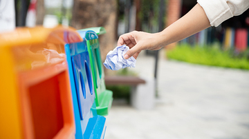 Hand placing crumpled paper into a colorful outdoor recycling bin
