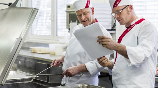 Two chefs reading notes in a kitchen