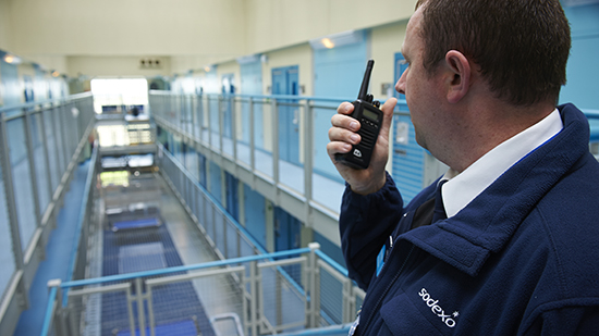 A male prison officer talking in to a walkie talkie