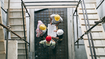 Quatre adultes sur un chantier de construction portant un casque et examinant des plans de construction, photographiés d'en haut