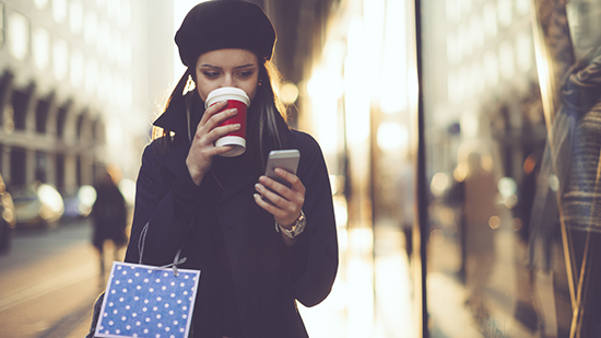 Person drinking a hot beverage, walking and looking at a smartphone