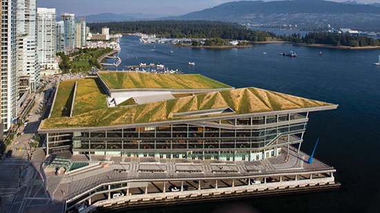 Conference center with grass on the roof next to a lake