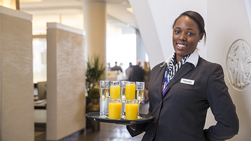 Air lounge hostess handing out drinks