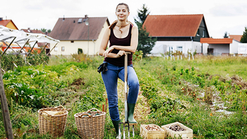 Female farmer standing with one leg on her garden fork
