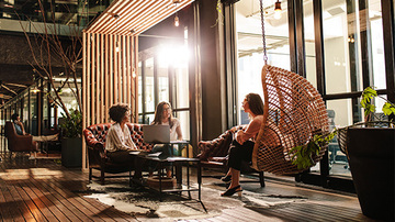 Three diverse young business women having an informal meeting in a comfortable, sunlit seating area