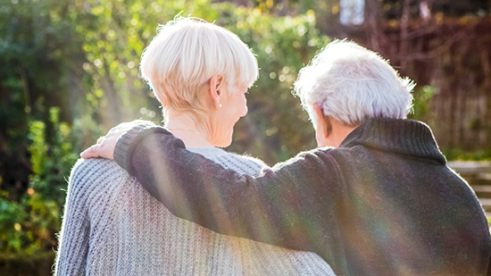 Two elderly people hugging each other, view from behind