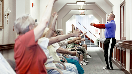 A Sodexo employee running an exercise to a row of seated elderly people