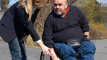 Man in wheelchair with female helper