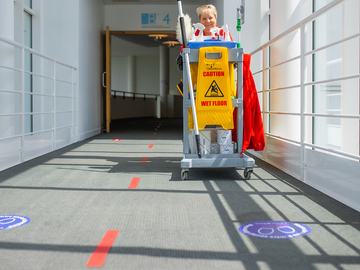 Cleaner pushing a cleaning cart wearing a mask