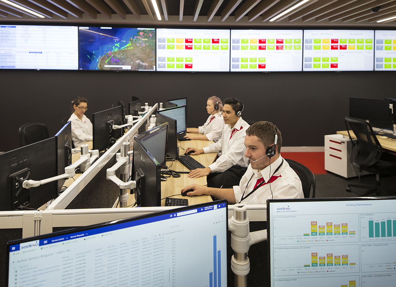 Sodexo employees in a call center with screens in the background
