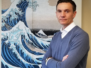 Mark Plumart in front of the painting The Great Wave Off Kanagawa