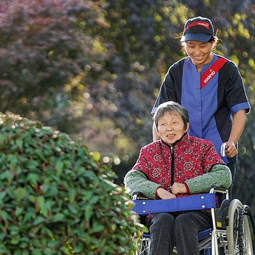 Sodexo nurse pushing elderly woman in a wheelchair through a garden