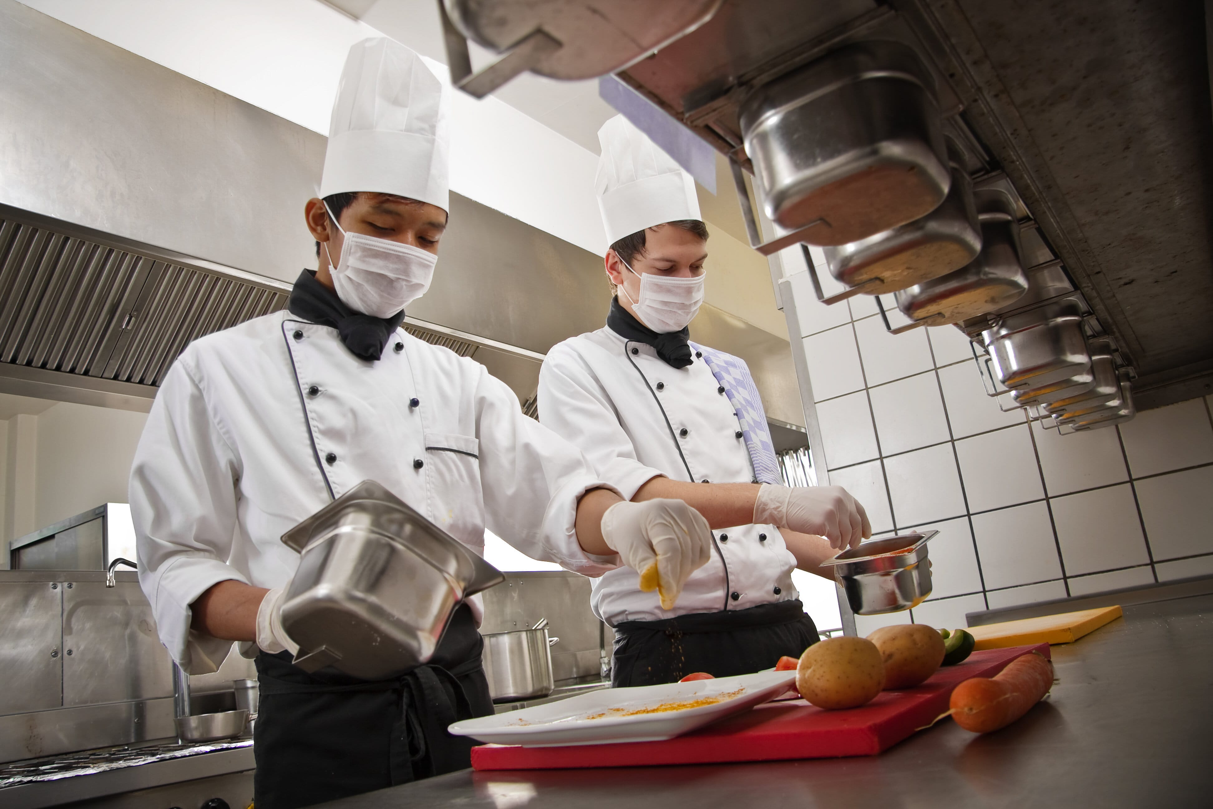 Two chefs preparing food wearing masks