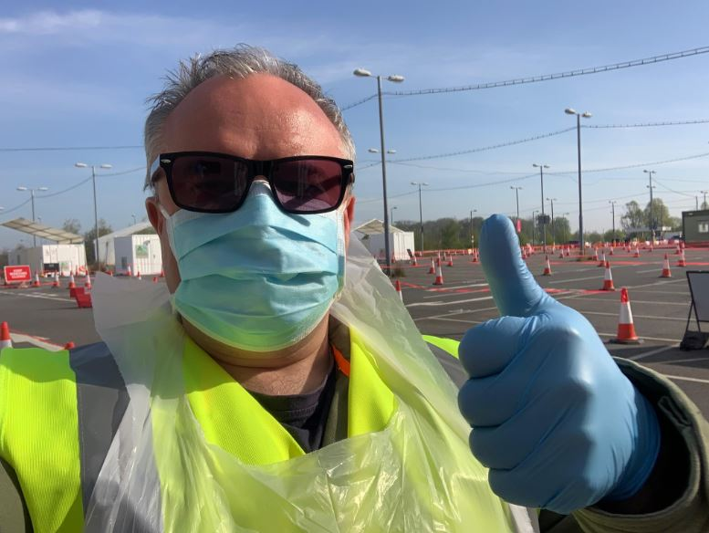 Man wearing protective gloves and mask, thumb up