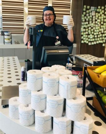 ProMedica Toledo Hospital employee holding toilet paper behind a cashier